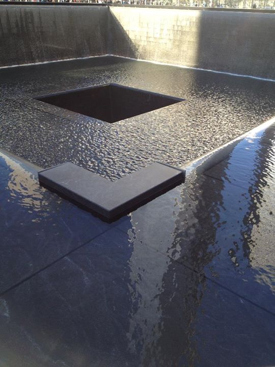 World Trade Center Memorial. One of the tower pools with the new WTC building in the reflection.